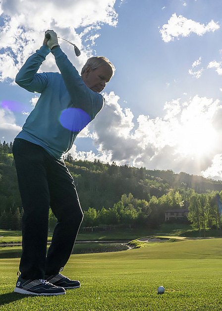 golfer swinging at ball with iron on fairway