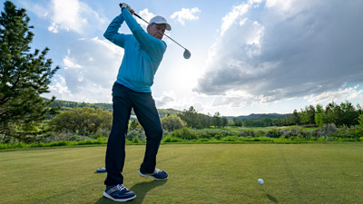 golfer swinging on tee box with driver