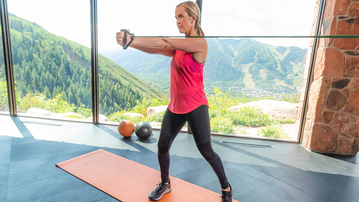 woman performing rotational training exercise to help golf game