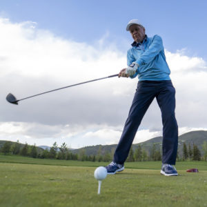golfer hitting ball on tee with driver