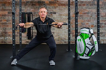 Using golf club to assist in golf fitness stretching exercises